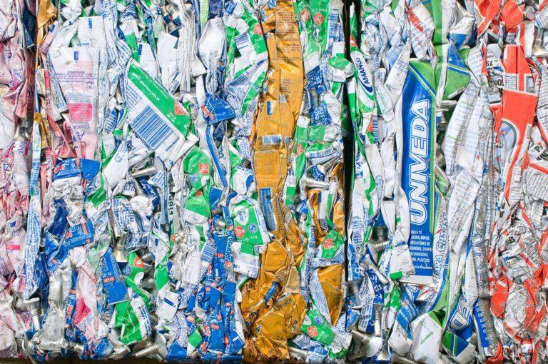 várias embalagens de alumínio e metal prensadas formando um mosaico de cores e grafismo