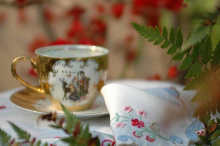 xicara dourada com motivos chineses, guardanapo bordado, com plantas e flores desfocadas ao fundo