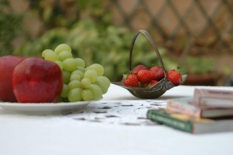 morangos em cestinha de metal antiga ladeada uvas e maçãs num prato e pequenos livros sobre a mesa com toalha rendada