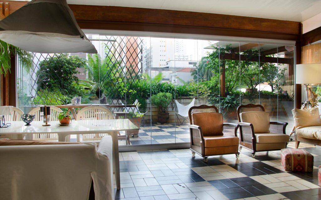 ambiente agradável com mesa, cadeiras e poltronas, envidraçado com vista para varanda externa repleta de plantas