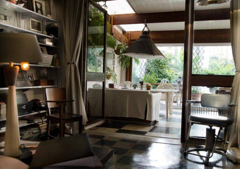 ambiente vintaje com abajur antigo em primeiro plano, cadeira de escola em madeira, olhando o terraço, separado por vidros,repleto de plantas
