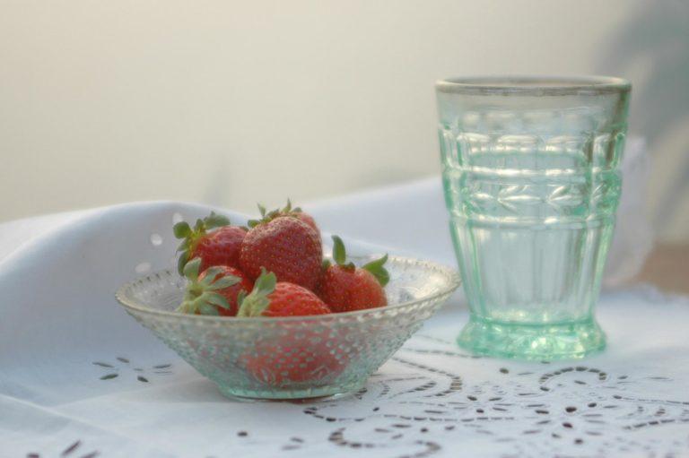 saladeira pequena com morangos ao lado de copo bisotado, ambos em vidro esverdeado, sobre toalha rendada