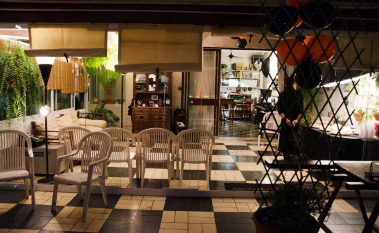ambiente vintage com iluminação quente, bexigas, plantas, cadeiras, mesa de buffet e garçom
