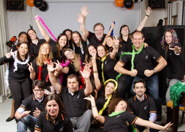 grupo de 21 pessoas posando para foto em clima animado, trajando acessórios de festa