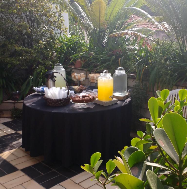 mesa com sucos, água, sanduiches, bolos, em terraço externo ladeado por plantas com luz de fim de tarde
