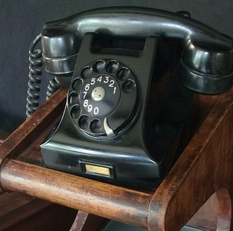 telefone antigo de disco preto, material baquelite, sobre móvel de madeira
