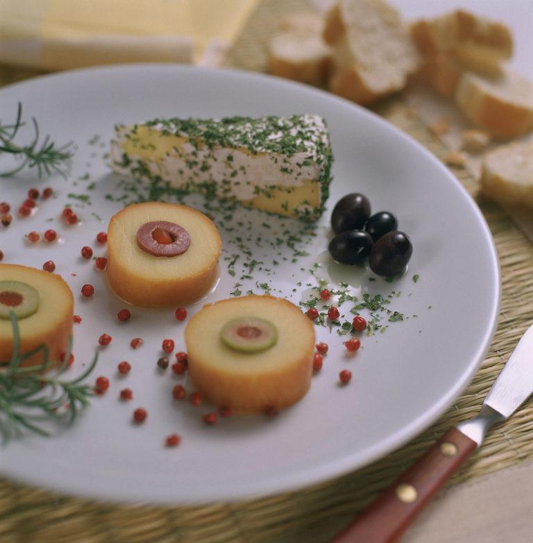 prato com fatias de queijo provolone recheadas com azeitonas verdes e pretas, atrás uma fatia de queijo brie salpicado com salsa fresca, pimentas em torno do prato, algumas azeitonas pretas e ramos de alecrim