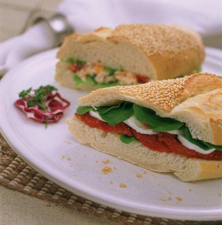 prato com sanduíche de tomate com queijoem primeiro plano e sanduíche de frango desfocado atrás