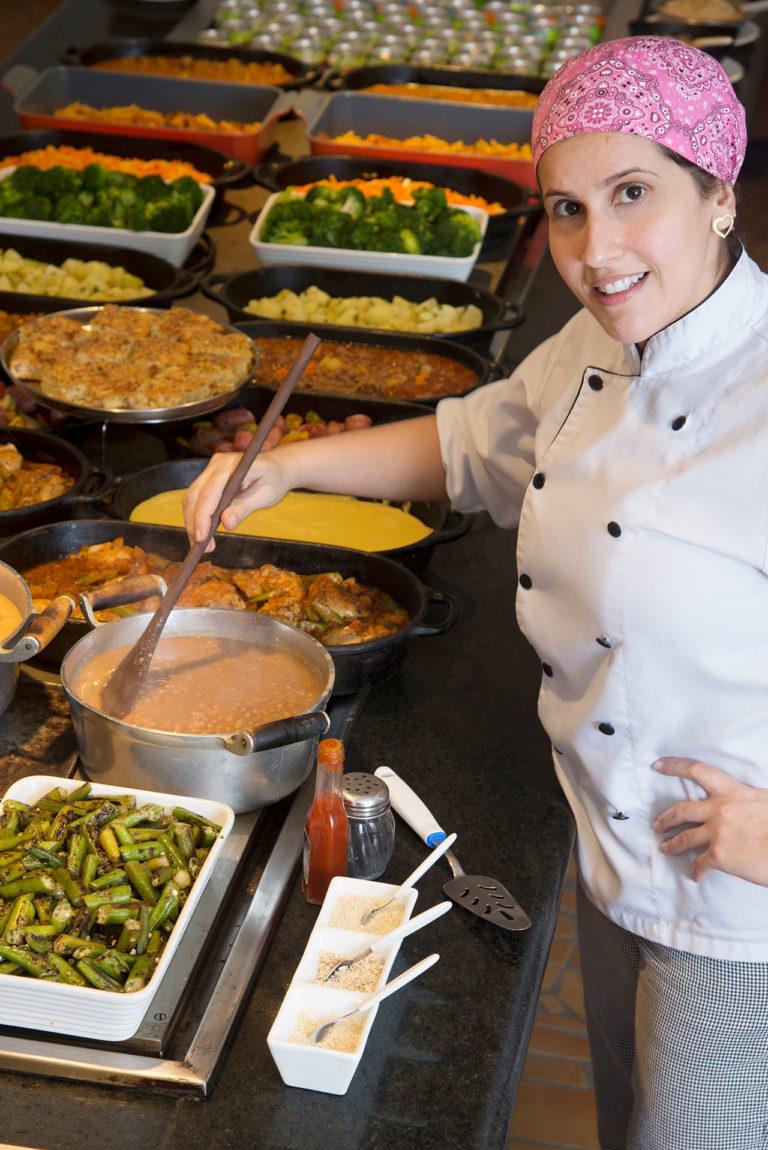 chefe de cozinha misturando feijão em panela, sobre variado buffet