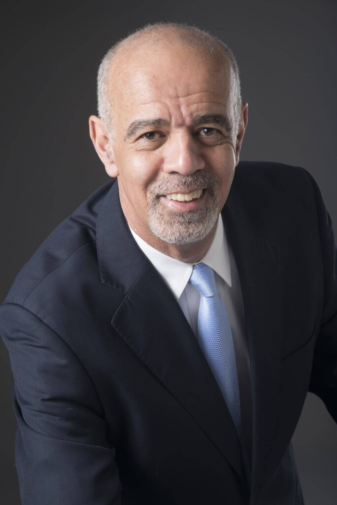 retrato profissional de homem de meia idade,sorrindo, com terno escuro e gravata azul, com luz dramática e fundo escuro