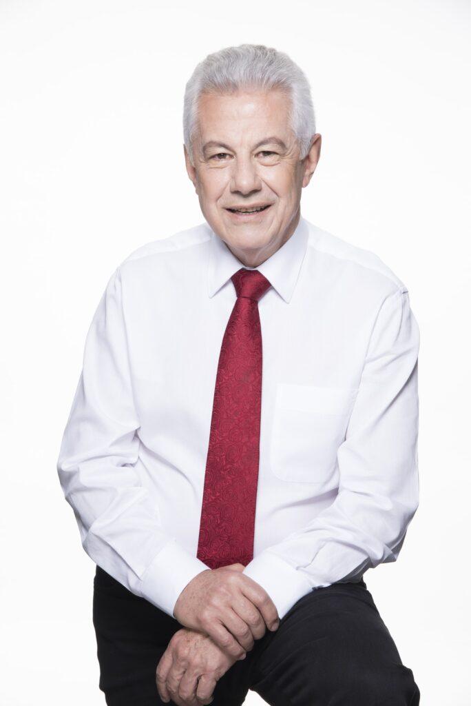 retrato profissional de homem de terceira idade, vestido com camisa branca e gravata vermelha, em ambiente claro
