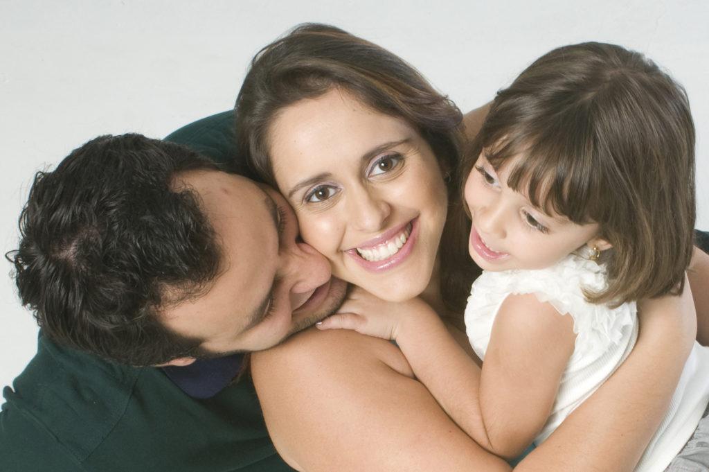 retrato familiar, mãe no meio, olhando para a lente da câmera, com filha no colo do lado direito e pai á esquerda olhando para a criança