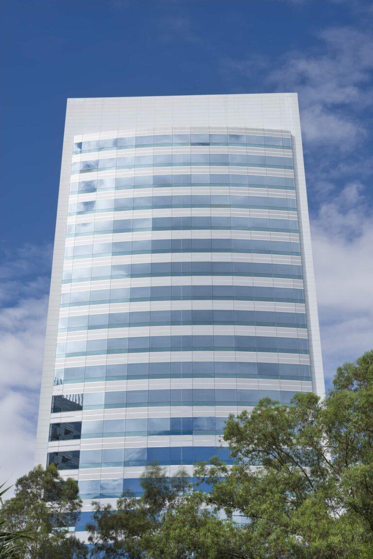 um prédio espelhado visto de baixo, espelhado nos vidros e sobre o prédio está um céu azul, e na base do prédio dá para ver os galhos de árvores com folhas verdes