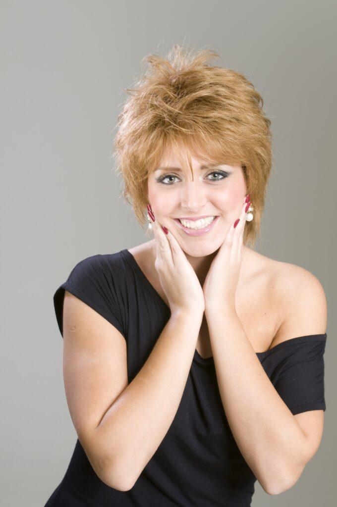 mulher jovem de cabelos curtos, com as mãos no rosto, sorrindo, ambiente de fundo cinza claro