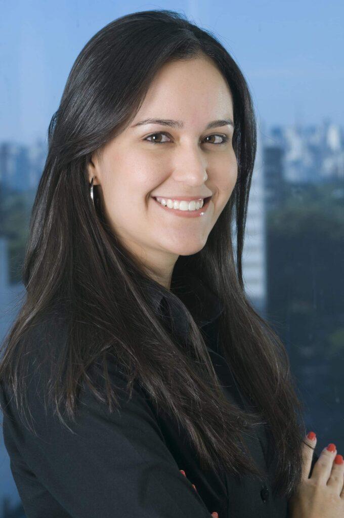 retrato profissional de mulher jovem branca, cabelos castanhos e lisos, sorrindo, á frente de uma janela