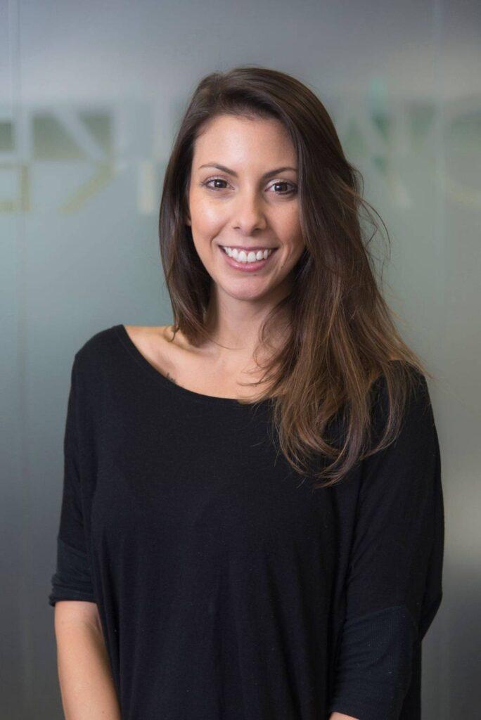 retrato profissional de mulher jovem de cabelos castanhos abaixo dos ombros, sorrindo, ambiente de escritório com fundo cinza desfocado