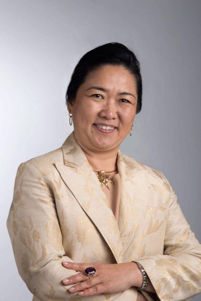 retrato profissional de mulher, sorrindo com os braços cruzados, vestida com blazer bege, em ambiente de fundo cinza claro