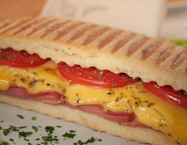 imagem focada no recheio de um sanduíche de mortadela, com muito queijo derretido, óregano e fatias de tomate em pão tostado