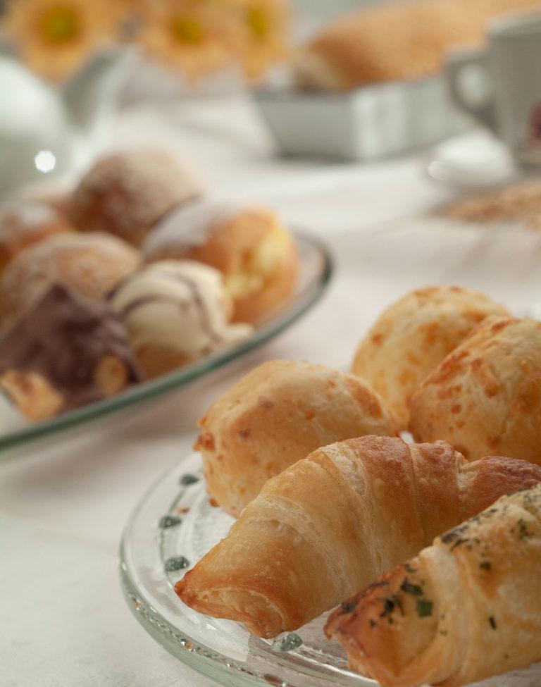 em primeiro plano, prato de vidro com croassants e pães de queijo, desfocados no fundo estão um prato com pães doces, travessa com outros pães, xícara, bule e jarro com flores amarelas