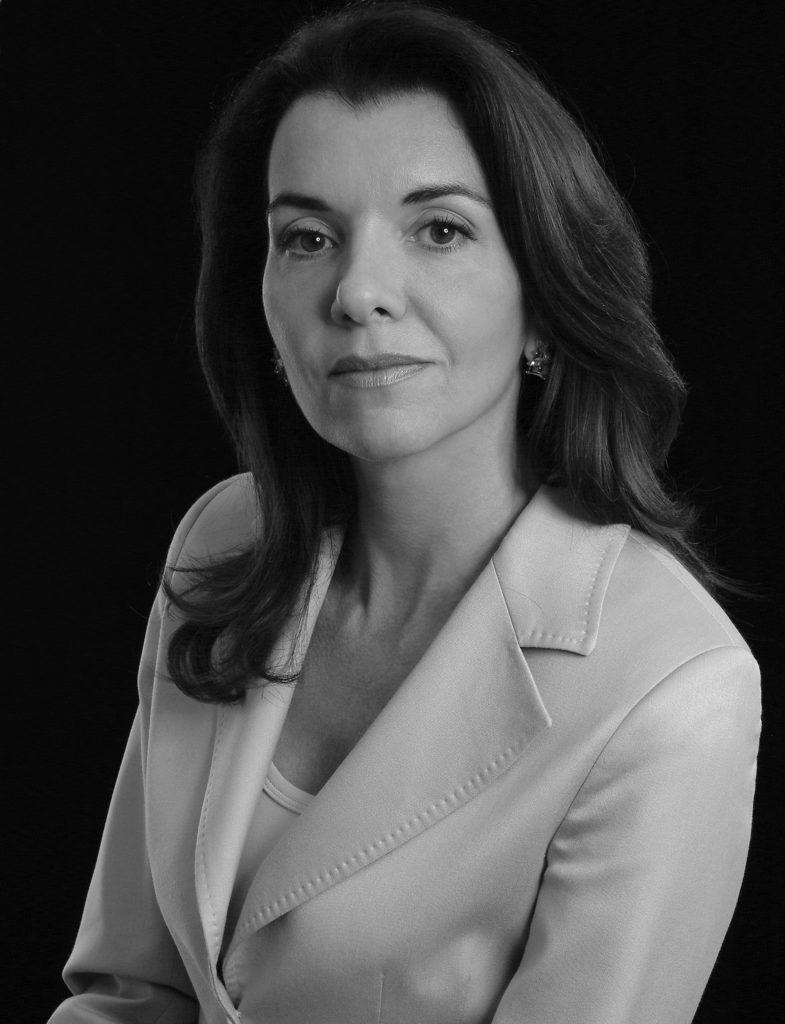 retrato profissional de mulher, pele clara e cabelos escuros pouco abaixo dos ombros, vestida com blazer claro, ambiente de fundo escuro, foto em preto e branco