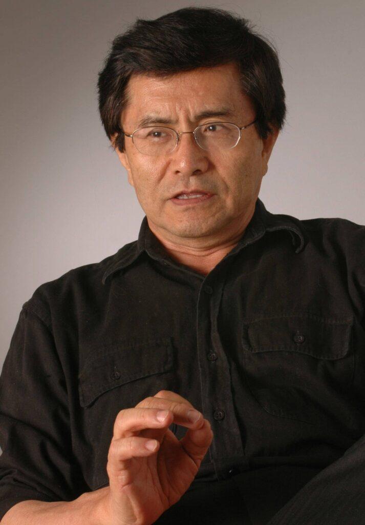 homem de meia idade, expressão de fala, com camisa preta em ambiente de fundo cinza claro
