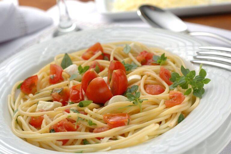 prato de espagueti com tomates e temperos, mesa posta desfocada ao redor com talheres, taças, travessa e guardanapo