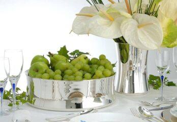 mesa posta com objetos de prata, travessa com uvas verdes, jarra de prata com arranjo de antúrios brancos, taças de vidro e talheres