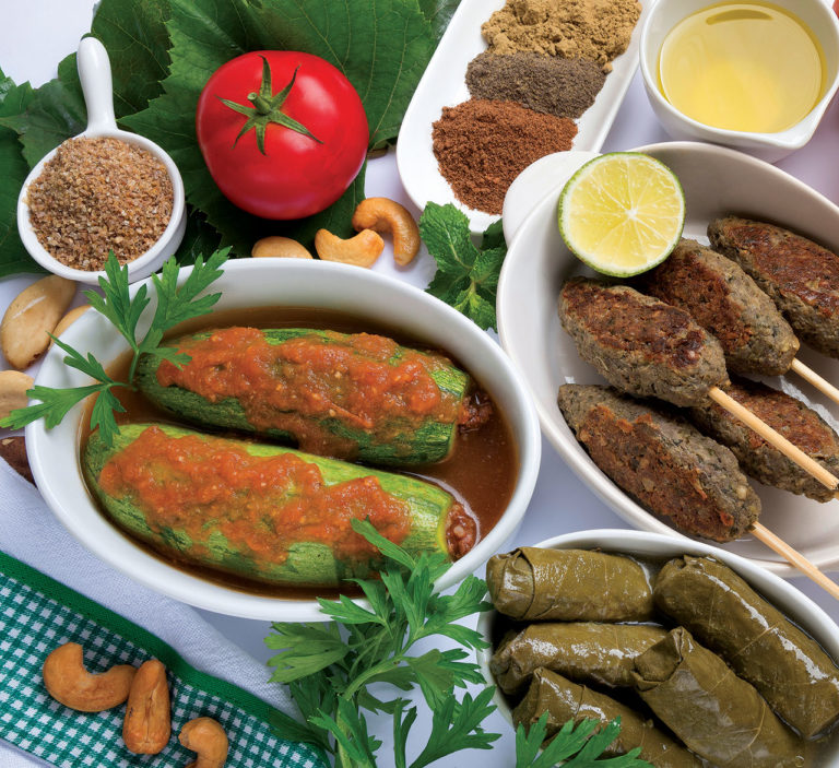 kibes no espeto, abobrinhas recheadas charutinhos de uva servidos em travessas e dispostos aleatoriamente ao redor, temperos, azeite, tomate e castanhas