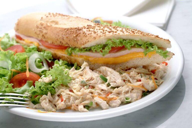 sanduíche baguete de peito de peru, chedar e salada, mostrando o recheio, no prato com salpicão de peru e salada