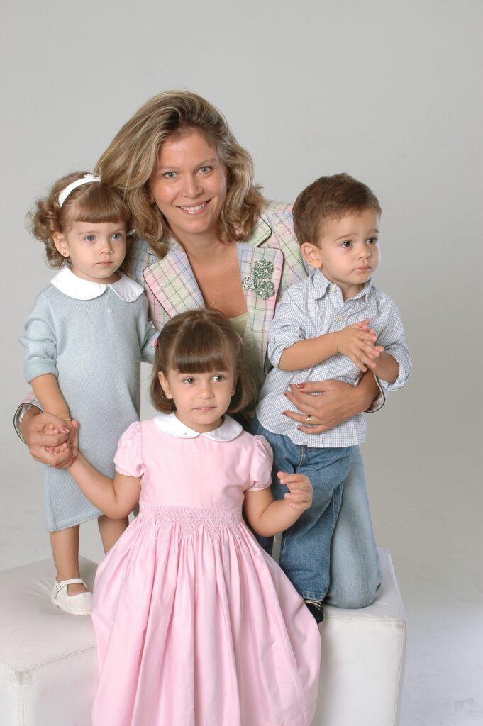 retrato familiar, mulher com 3 filhos pequenos ao seu redor, os dois menores nas suas laterais sobre puffs branco e a criança maior á sua frente, ambiente claro