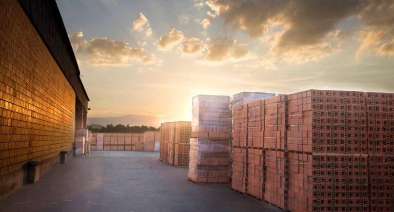 área externa de fábrica, com pilhas altas de blocos de cerâmica, cena iluminada com pôr do sol