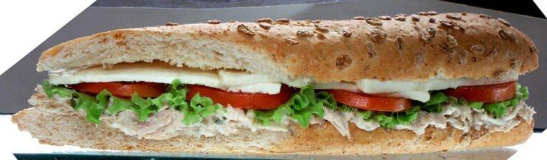 sanduíche de patê de atum, com alface, tomate e queijo, em um pão de grãos