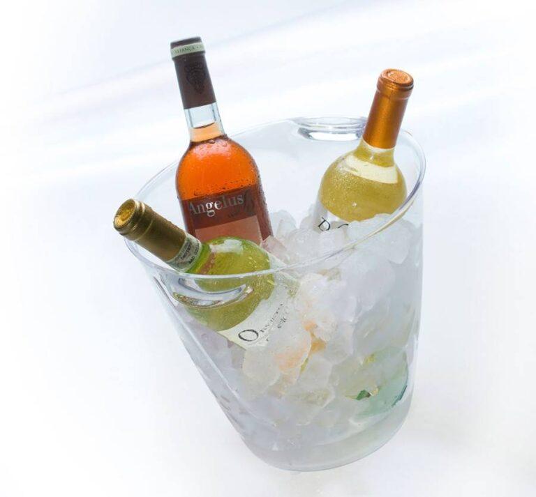 balde transparente com gelo e três garrafas de bebidas