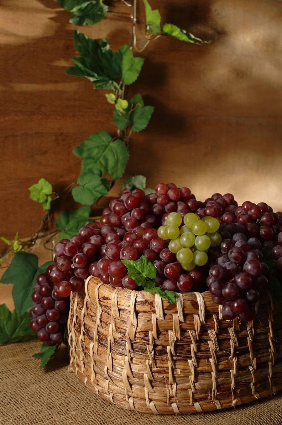 cesta com uvas, fundo em madeira com folhas