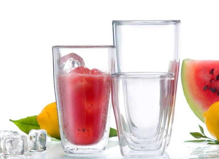 3 copos de vidro, suco de melancia, fatia de melancia, limão siciliano, cubos de gelo, em fundo branco