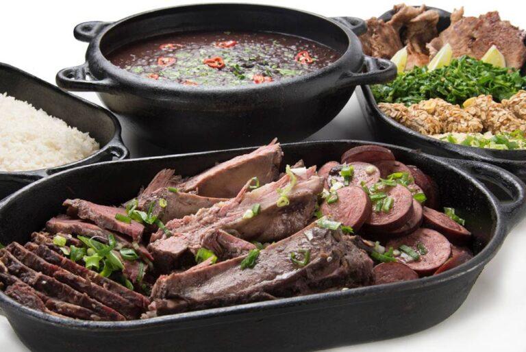 carnes da feijoada em travessa à frente, panela com feijão preto atrás e duas travessas nas laterais com arroz e acompanhamentos