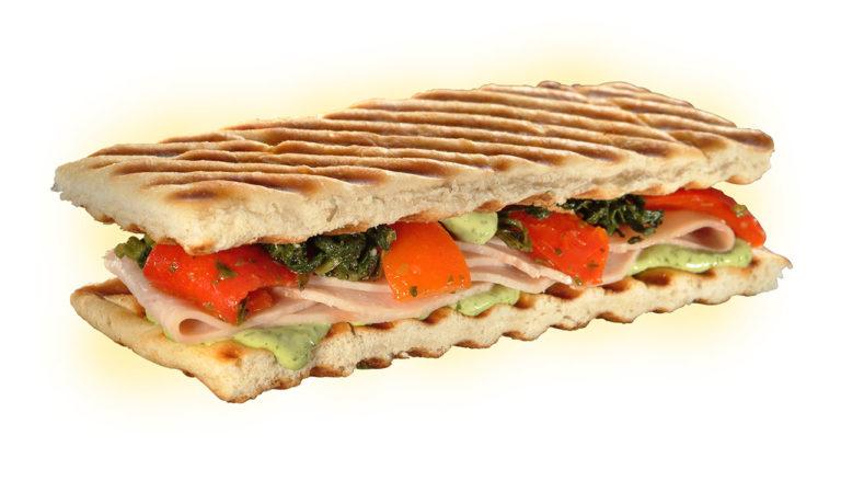 sanduíche de peito de peru com maionese temperada, folhas verdes de legumes e cenouras lâminadas refogados sobre as fatias de peito de peru