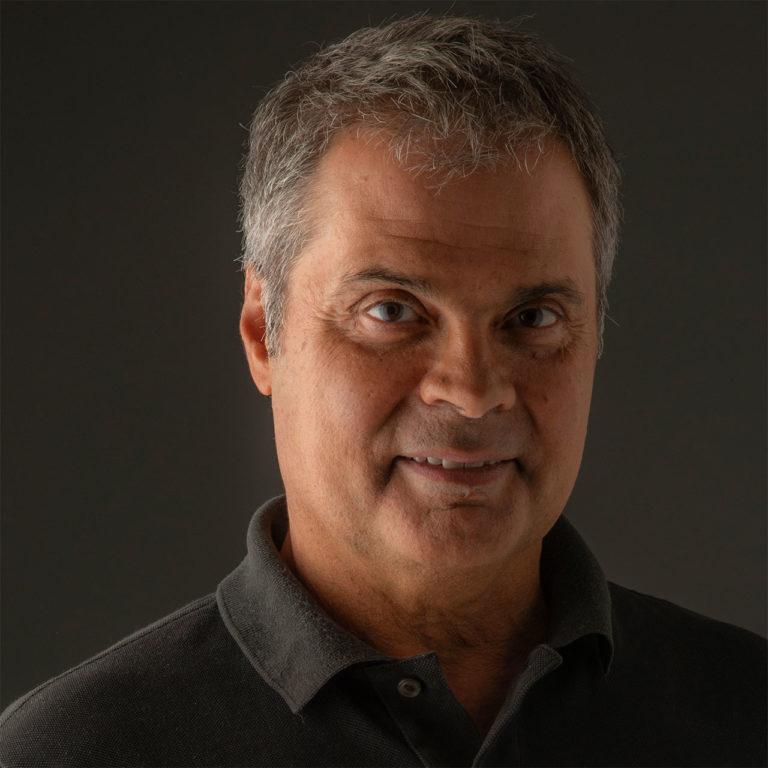 homem de meia idade, com leve sorriso, de camisa polo preta em ambiente de fundo cinza, com luz dramática