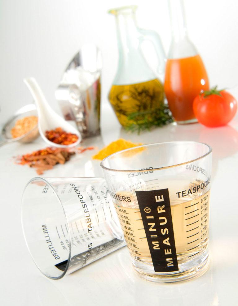 2 frascos desadores em primeiro plano, no fundo desfocado tem um jarro de azeite, de extrato de tomate e temperos