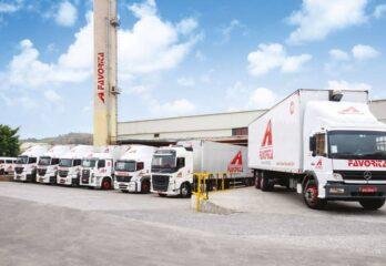 7 caminhões da empresa estacionados paralelamente em pátio da empresa