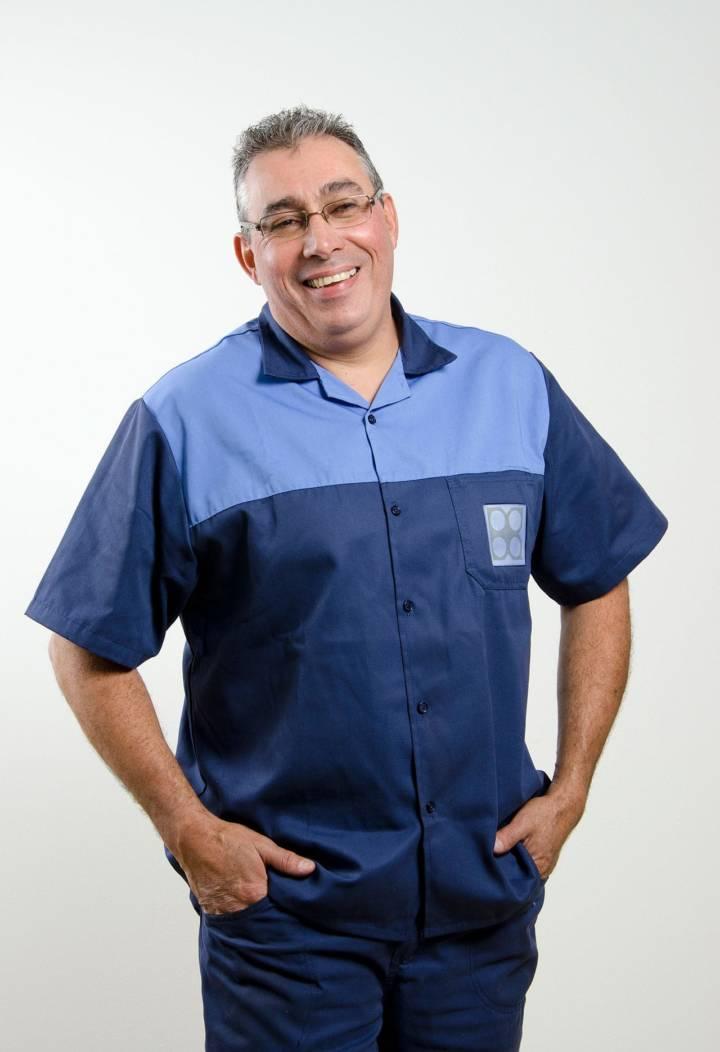funcionário, sorrindo, com uniforme da empresa, mãos no bolso, fundo branco
