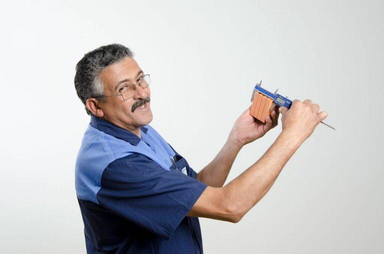 funcionário uniformizado segurando bloco de cerâmica e medidor de precisão
