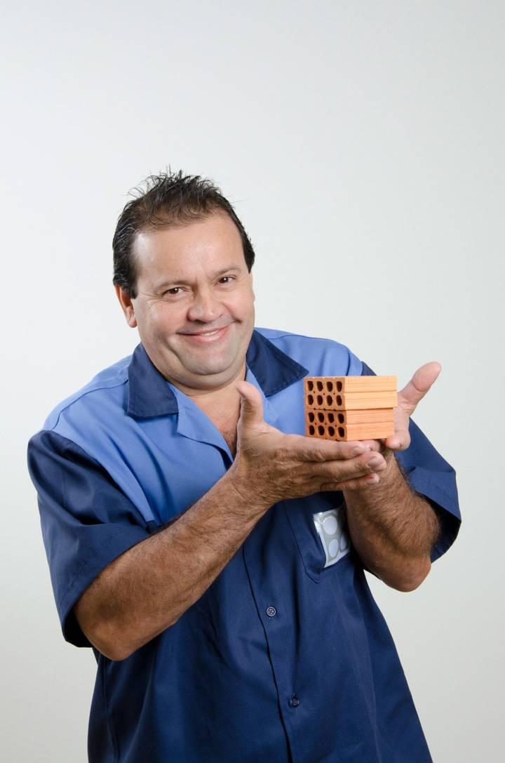 funcionário uniformizado segurando blocos de cerâmica em miniatura