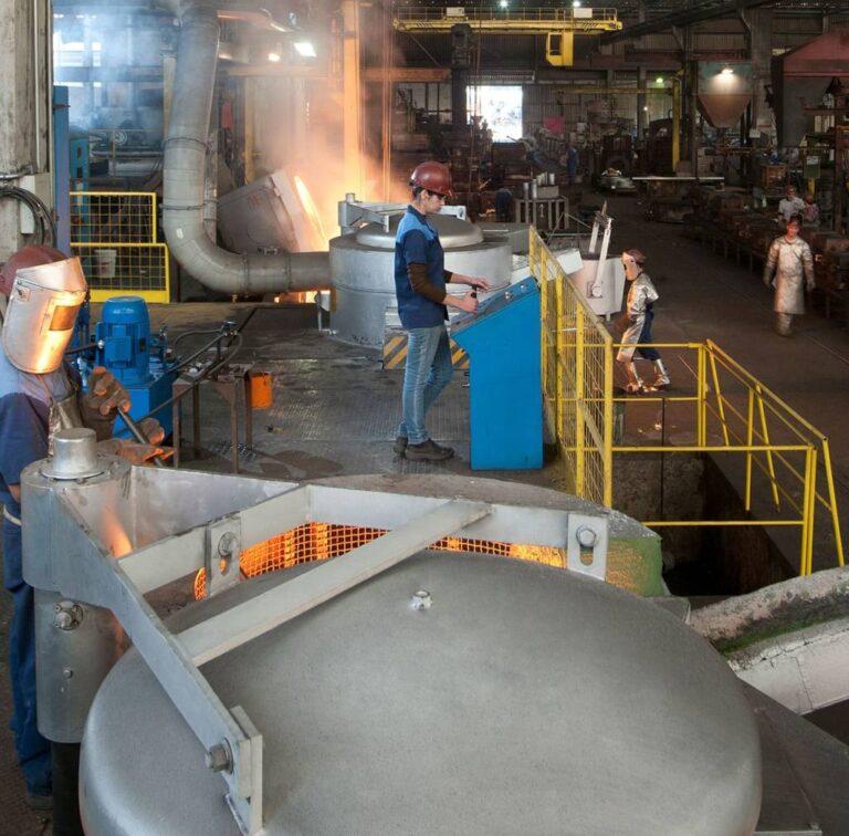 ambiente de fábrica com caldeirão, funcionários em ações rotineiras