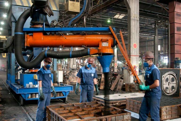 ambiente de fábrica, com 3 funcionários uniformizados em ação