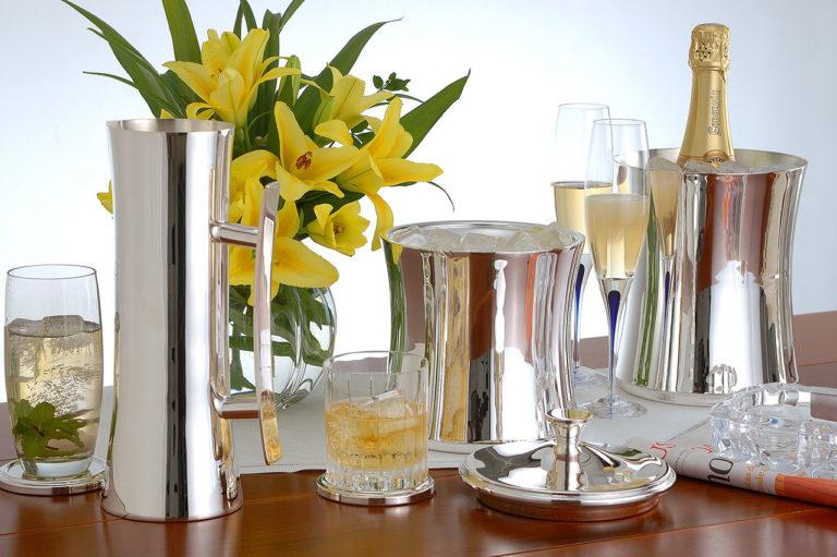 pratarias, copa com bebidas, arranjo de flores, garrafa de champagne e arranjo de flores, em superfície de madeira