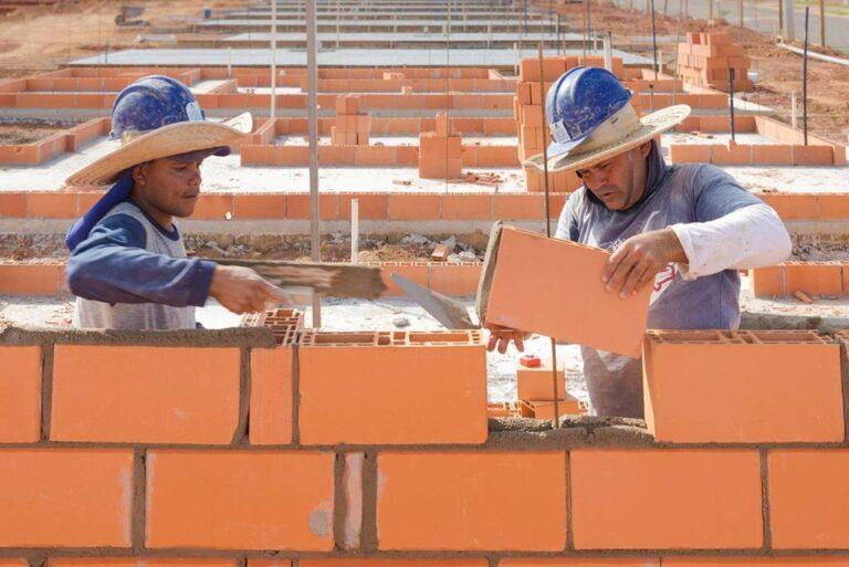 empreiteiros posicionando bloco para construção de parede
