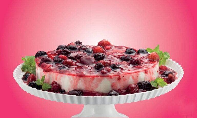 travessa redonda de base suspensa com sobremesa regada com calda de frutas vermelhas com pedaços das frutas, alguns ramos de hortelã nas bordas da travessa, fundo da imagem rosa