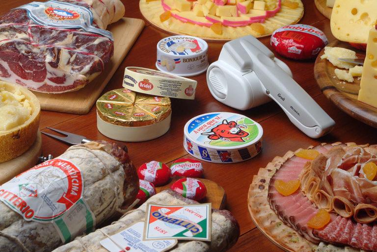 queijos inteiros e em pedaços, frios, peça de carne, salames e alguns utensílios sobre mesa de madeira