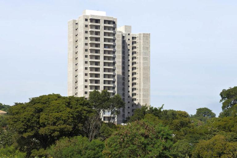 foto perspectivada de prédio em construção em área bem arborizada